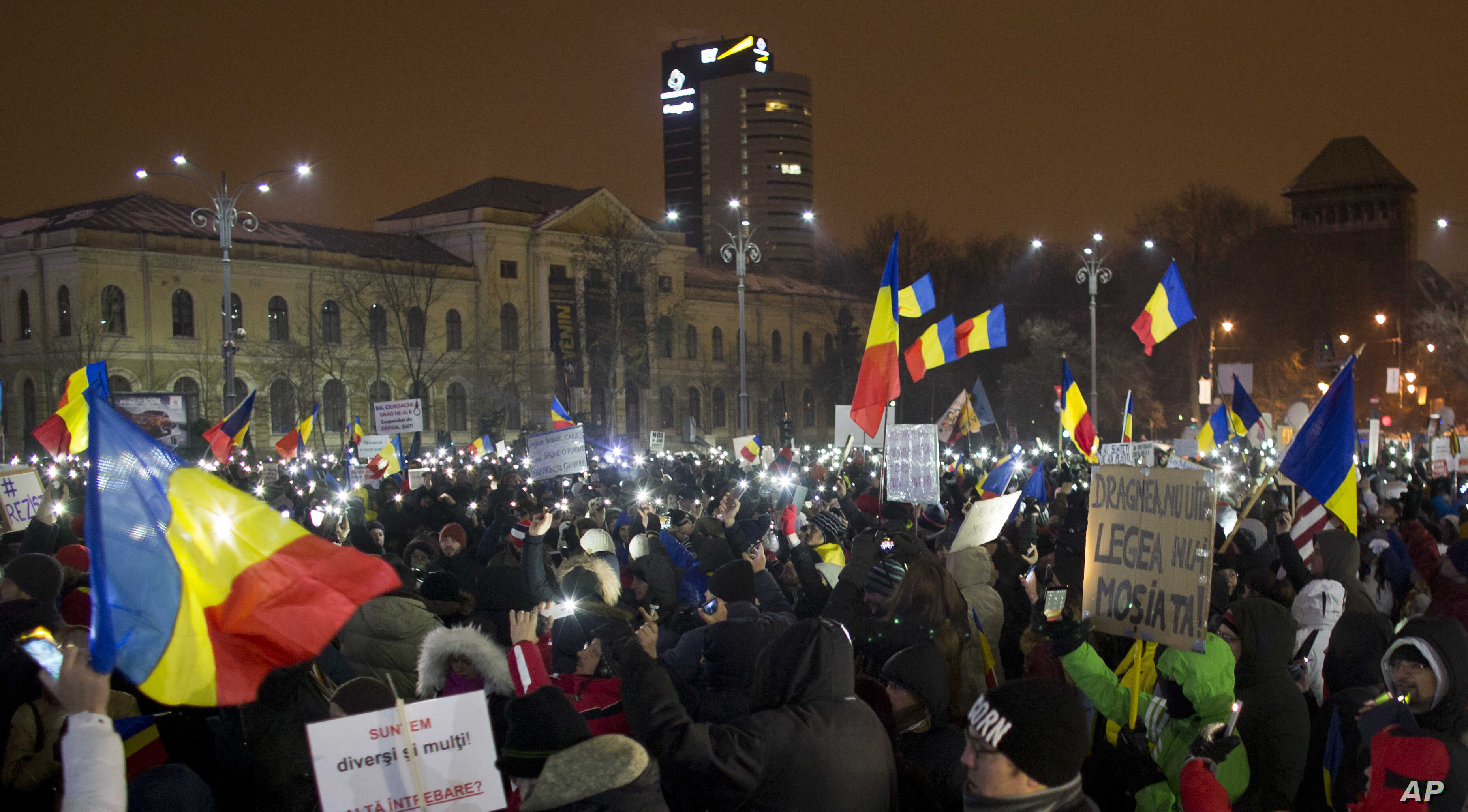 Protesters lit torches and wave flags as they gather outside the government building in Bucharest, Romania, Feb. 11, 2017.
