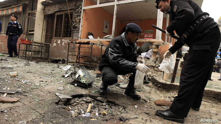 Policemen collect evidence from the site of a bomb attack at the district court in Islamabad, Mar. 3, 2014.