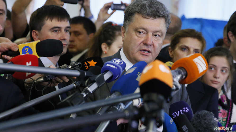 """FILE - Ukrainian President Petro Poroshenko (C), a presidential candidate at the time, speaks to journalists in Kyiv, May 25, 2014. Recently, Poroshenko has raised eyebrows urging journalists not to write """"negative articles about Ukraine."""""""