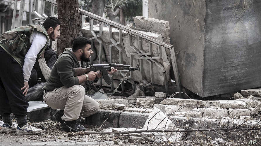 Syrian rebel fighters take cover as a Syrian army sniper aims over a destroyed mosque in Tarik Al-Bab, southeast of Aleppo, October 26, 2012.