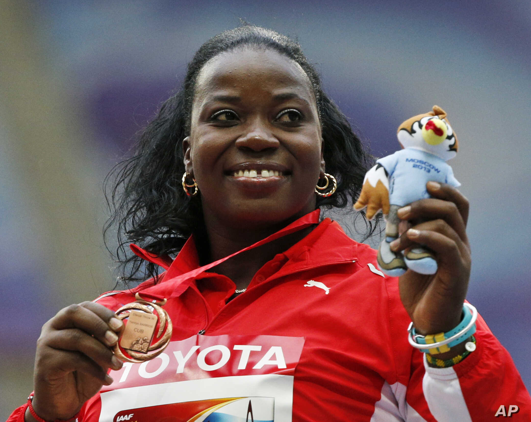 FILE - Cuba's Yarelys Barrios poses with her bronze medal for the women's discus throw during the medals ceremony at the World Athletics Championships in the Luzhniki stadium in Moscow, Russia, Aug. 12, 2013. She was stripped of the silver medal in t