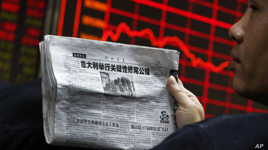 A man reads a newspaper as he looks at an electronic board displaying stock prices at a brokerage house in Beijing, Dec. 5, 2016.