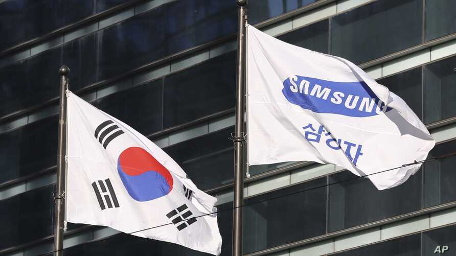 The company flag of Samsung Electronics (R) flutters next to the South Korean national flag in Seoul, South Korea, Jan. 16, 2017