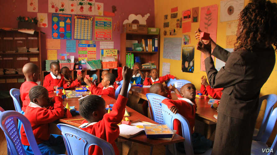 A teacher at the Kibera School for Girls teaches students about shapes in Nairobi, Kenya, March 19, 2013. (J. Craig/VOA)