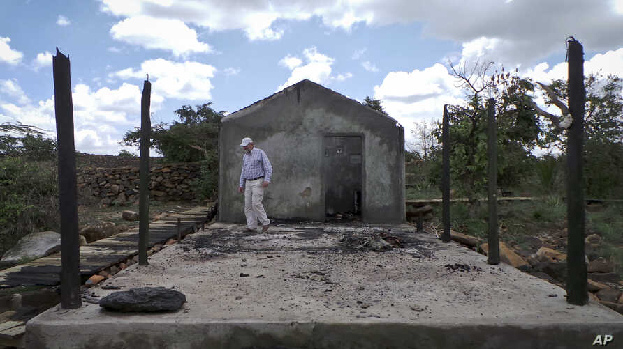 Farmer Martin Evans inspects a blackened home, burned down during an invasion by semi-nomadic herders on his property in Laikipia, Kenya, July 27, 2017.