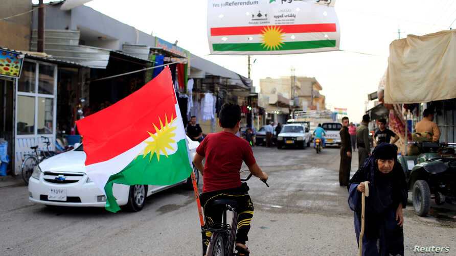 A boy rides a bicycle with the flag of Kurdistan in Tuz Khurmato, Iraq, Sept. 24, 2017.
