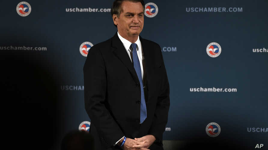 Brazilian President Jair Bolsonaro stands as he is applauded after speaking at the Chamber of Commerce in Washington, March 18, 2019.
