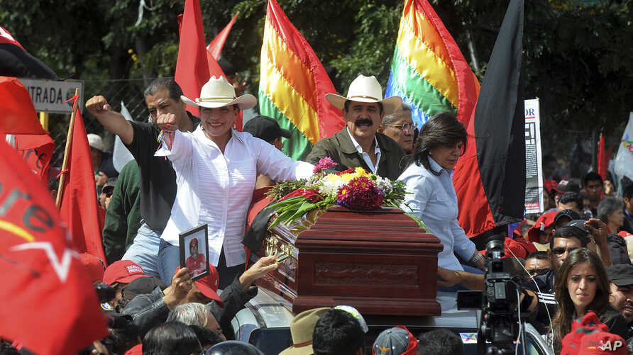 Presidential candidate Xiomara Castro, left, and her husband, Manuel Zelaya, ride on the roof of a car with a coffin containing the body of a supporter that was killed a day earlier by alleged criminals during a protest march in the capital city of T