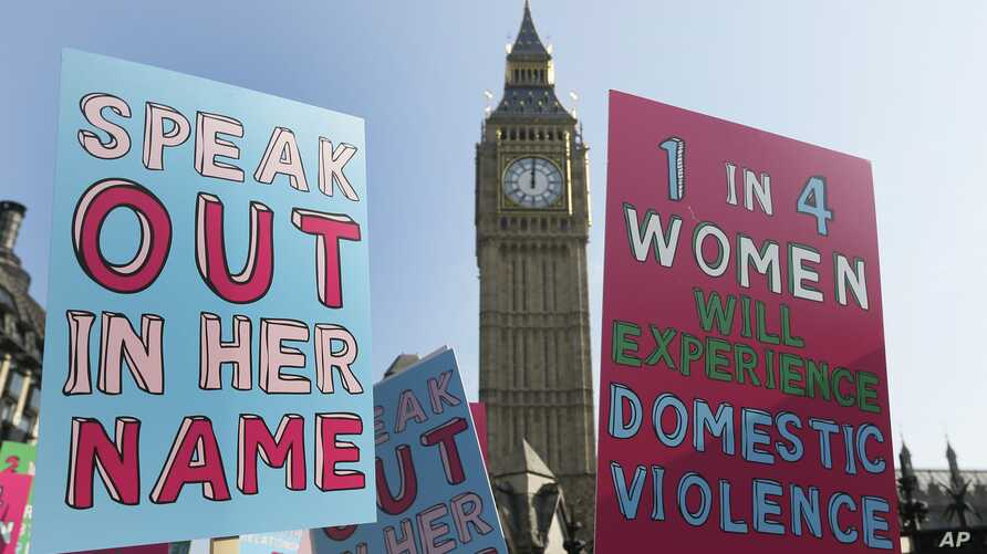 FILE - People hold banners during a demonstration against domestic violence near Big Ben in London, March 5, 2013.