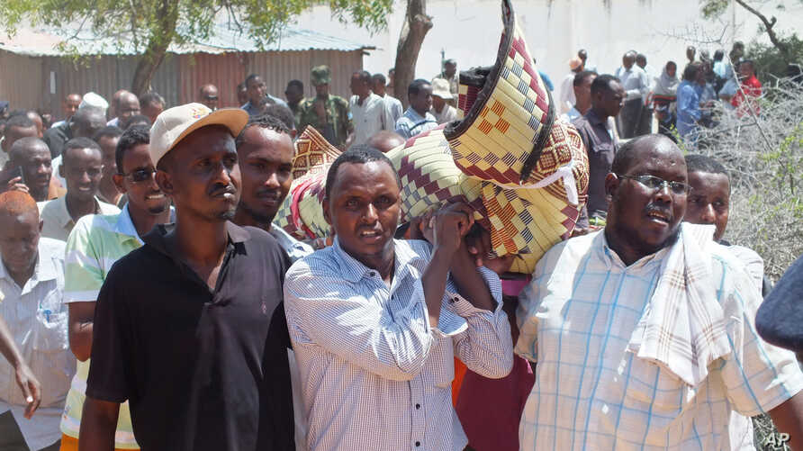 Mourners carry the body of Somali lawmaker Abdiaziz Isaq Mursal for burial in the Somali capital, Mogadishu, Tuesday April 22, 2014.