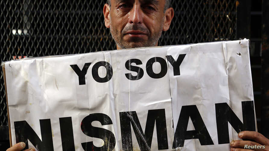 """Marcelo Novillo, whose son Adrian was a victim of a violent crime, cries as he holds up a sign that reads """"I am Nisman"""" outside the office of the prosecutor who is investigating the death of prosecutor Alberto Nisman in Buenos Aires January 22, 2015."""