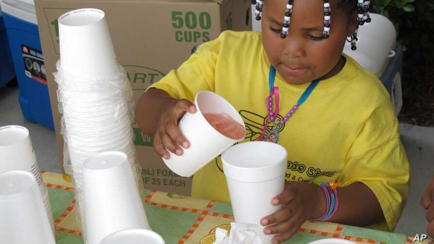 FILE - Harmonie Fredrick pours lemonade at a stand in Columbia, S.C., May 25, 2011. In North Carolina, authorities have arrested a man suspected of robbing a young lemonade vendor at gunpoint.