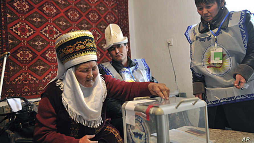Election commission officials wait as an elderly Kyrgyz woman, left, casts her ballot at home in the village of Kizil Birlik, 25 km (14 miles) south of Bishkek, Kyrgyzstan, October 29, 2011.