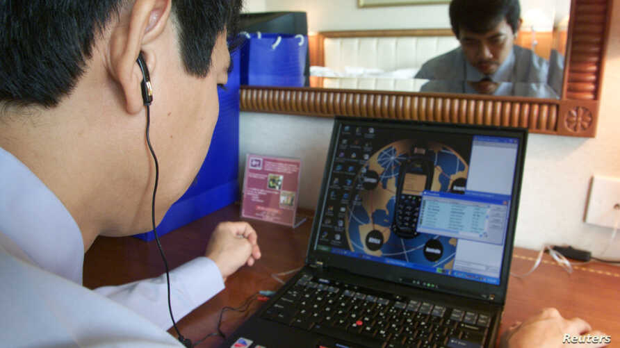 """FILE - Tran Huynh Duy Thuc, founder of a Vietnamese Internet provider, makes a telephone call via the Internet in his office in Hanoi, July 3, 2003.Ho Chi Minh City is quickly becoming a destination for """"tech nomads"""" – online entrepreneurs looking to"""