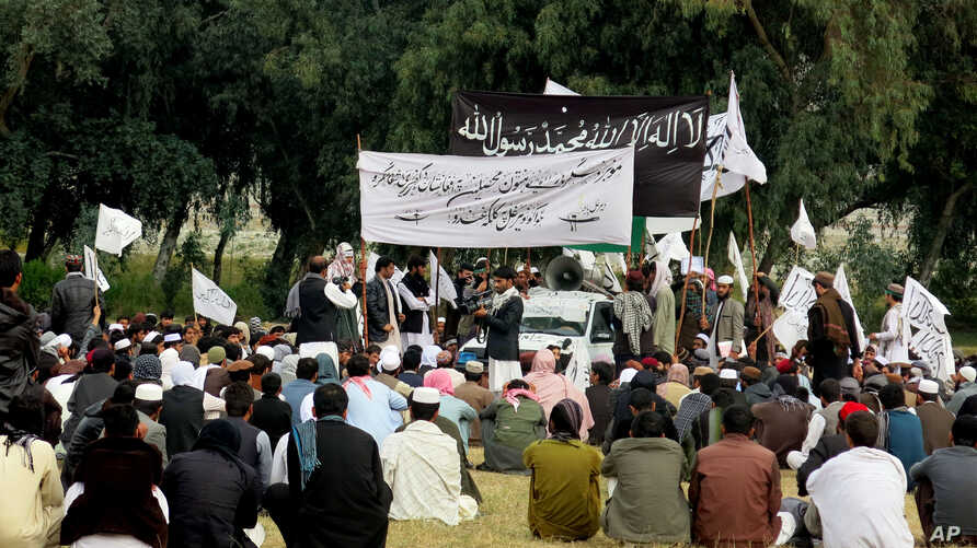 FILE - Nangarhar University students gather as some raise Taliban and Islamic State flags in Jalalabad, Afghanistan, Nov. 8, 2015. An Afghan official said the government is investigating links between universities and extremist groups.