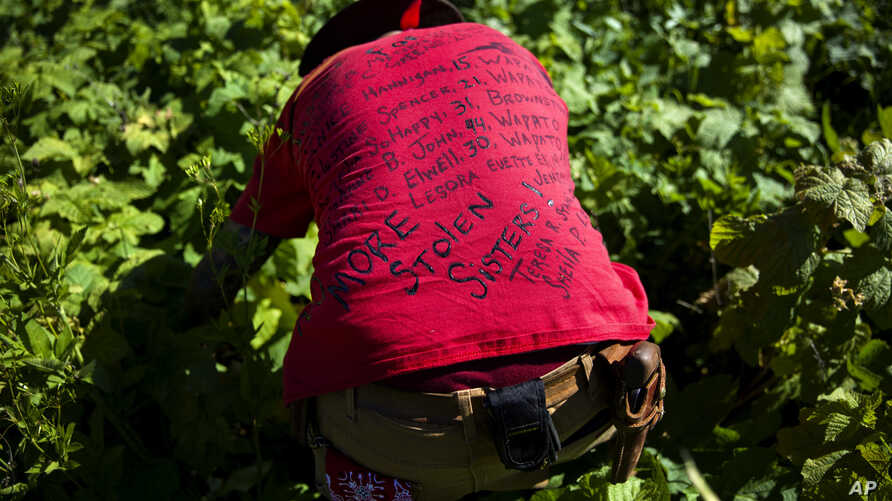 FILE - Randy Ortiz wears a shirt with the names of missing and murdered indigenous women as he searches for Ashley HeavyRunner Loring in the mountains of the Blackfeet Indian Reservation in Babb, Mont., July 12, 2018. On some reservations, Native Ame