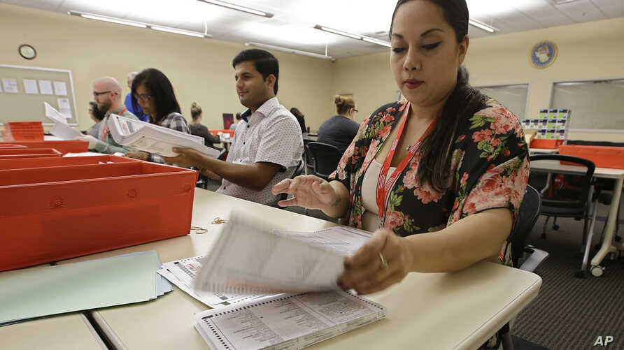FILE -Bianca Savola, an election clerk at the Sacramento County Registrar of Voters, inspects mail-in ballots in Sacramento, Calif., May 30, 2018.