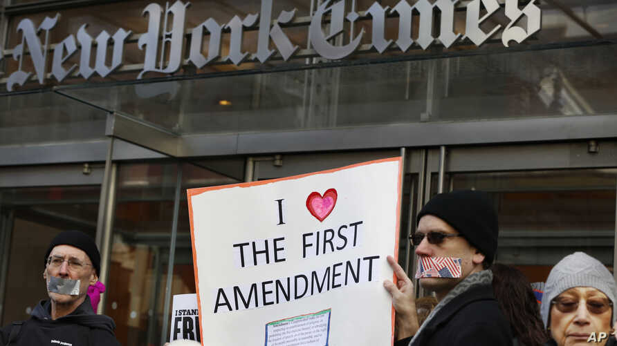 FILE - Protesters hold signs during a show of solidarity with the press in front of The New York Times building, Feb. 26, 2017, in New York.
