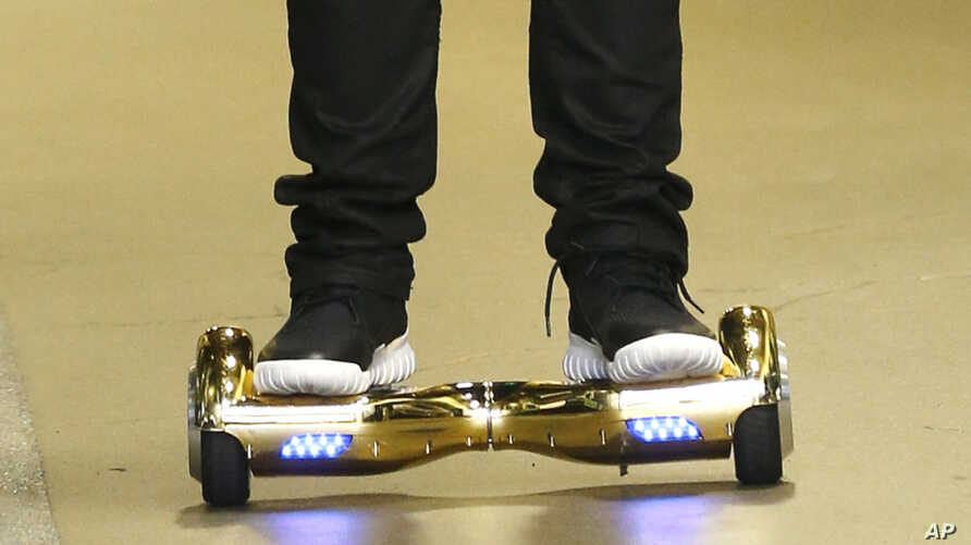 FILE - Seattle Seahawks wide receiver B.J. Daniels rides a hoverboard as he arrives for an NFL football game against the Carolina Panthers, in Seattle. Amazon is warning British customers that their hoverboards may be unsafe, the latest in a string o