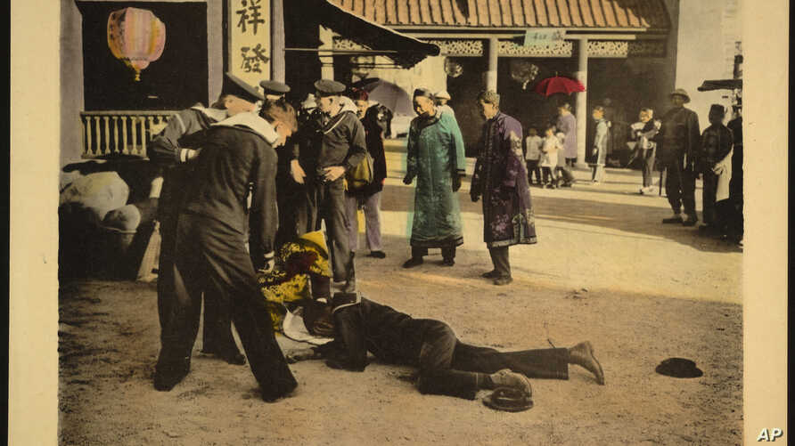 "This undated handout image provided by the Library of Congress shows a motion picture lobby card for D.W. Griffith's ""Broken Blossoms"" (1919), showing sailors standing over two bodies, lying on the dirt street in Chinatown."