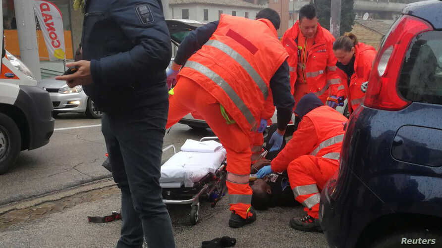 Health care personnel help an injured person after being wounded by gunfire from a vehicle in Macerata, Italy, Feb. 3, 2018.