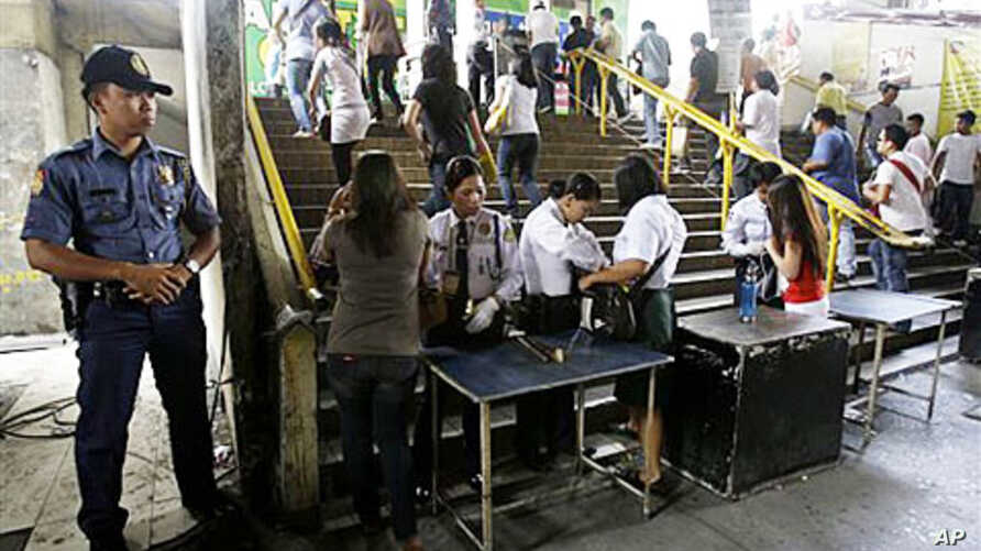 A Filipino policeman stands guard as security guards inspect the bags of passengers at a commuter train station in suburban Manila, Philippines, 26 Jan 2011