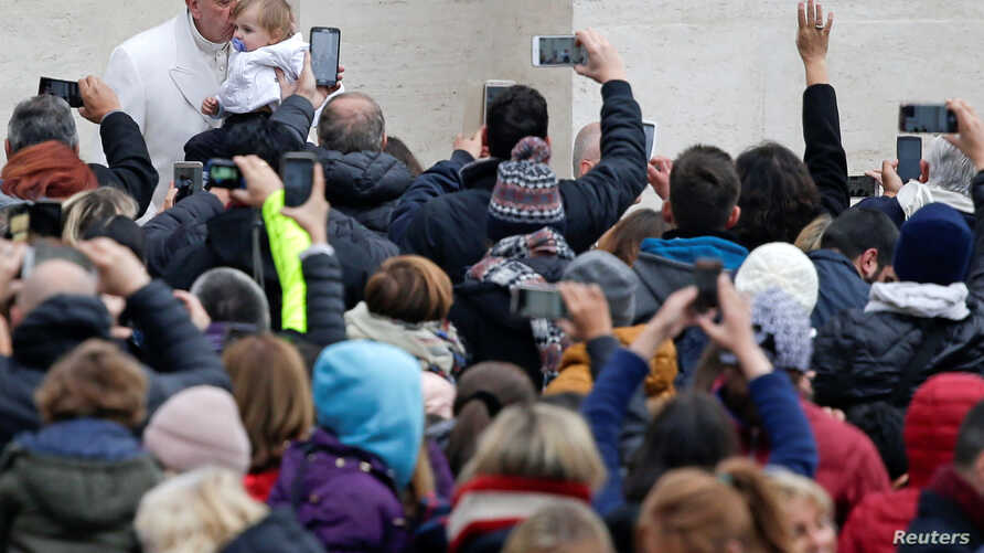 Pope Francis kisses a baby as he leads the weekly general audience in Saint Peter's Square at the Vatican, Feb. 22, 2017.