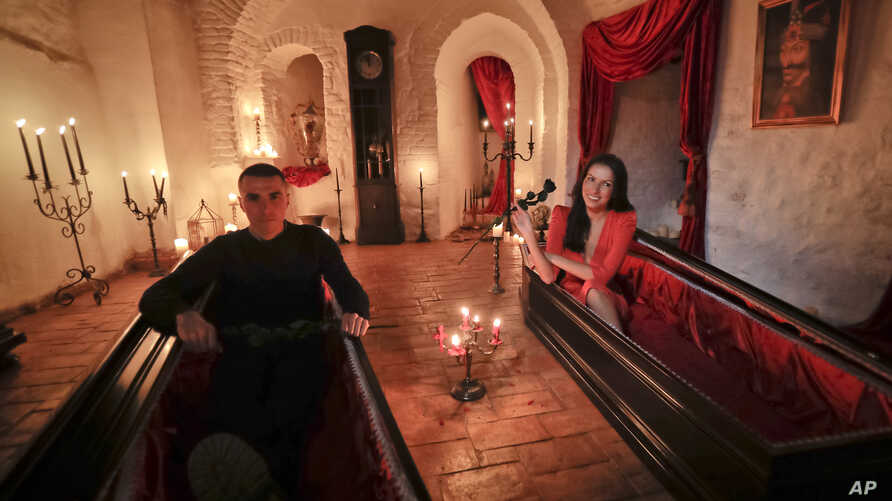 Tami Varma (R) and her brother Robin, grandchildren of a scholar of English gothic tales and an expert in vampire lore, pose in coffins at Dracula's Castle, in Bran, Romania, Oct. 31, 2016. The pair bested 88,000 people in a competition to win the ch