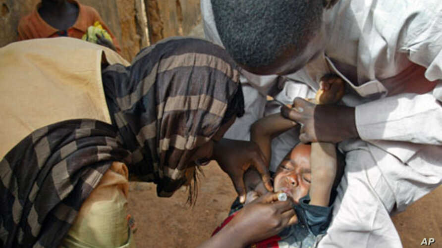 Volunteers administer polio vaccine to a child in Kaduna, Nigeria, (File)