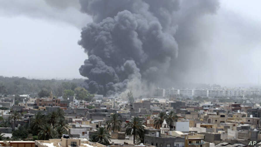 Smoke rises after coalition air strikes in Tripoli June 7, 2011.