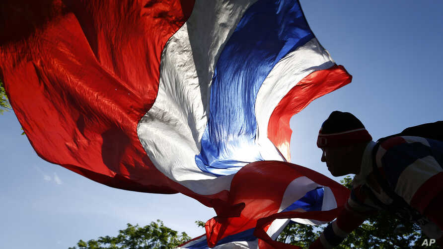 An anti-government protester waves a Thai national flag during a rally in downtown Bangkok, Thailand, May 9, 2014.