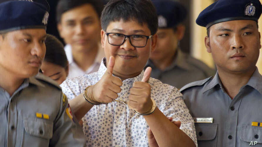 Reuters journalist Wa Lone, center, gives a thumbs up sign as he is escorted by police upon arrival at the court for trial in Yangon, Myanmar Friday, April 20, 2018.