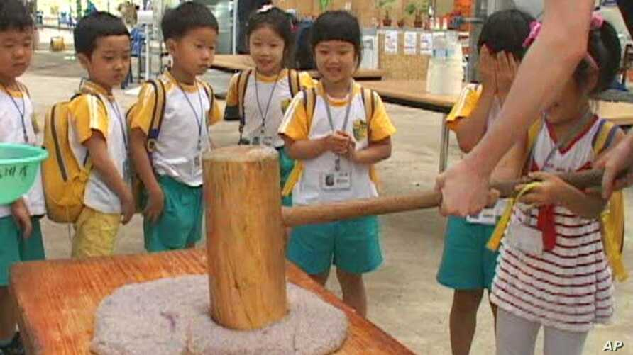 Summer camp kids get a hand with an old Asian tradition, with a twist - pounding rice cakes infused with blueberry juice