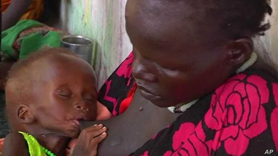 In this photo taken from Video provided by Associated Press on Tuesday, May 13, 2014,  a malnourished child is fed by her mother,  in a Medecins Sans Frontiers (Doctors Without Borders) hospital, in Leer, South Sudan.  Bodies stuffed in wells. Houses