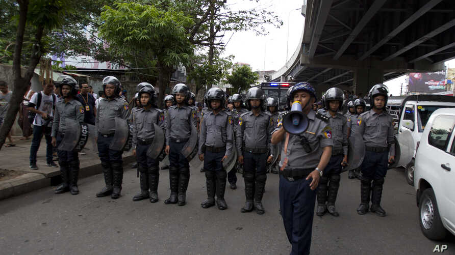 FILE - Police officers stand in position to block activists during a rally in Yangon, Myanmar, May 12, 2018.