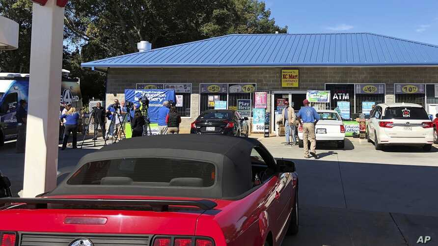 FILE- Media, at left, record people entering the KC Mart in Simpsonville, S.C., after it was announced the winning Mega Millions lottery ticket was purchased at the store, Oct. 24, 2018.