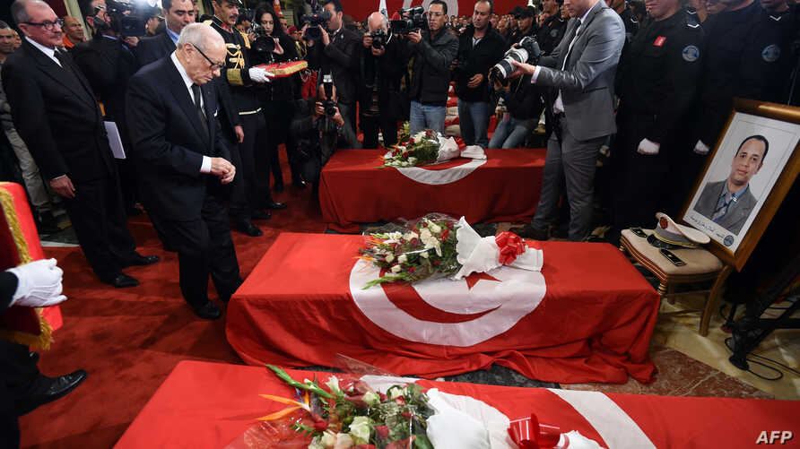 Tunisian President Beji Caid Essebsi decorates members from the presidential guards who were killed in a bomb blast on a bus in central Tunis the previous day during a ceremony at Carthage Palace, Tunis, Nov. 25, 2015.