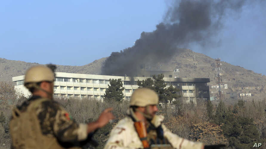 Afghan security personnel stand guard as black smoke rises from the Intercontinental Hotel, Jan. 21, 2018, after an attack in Kabul, Afghanistan. Gunmen stormed the hotel and set off a 12-hour gun battle with security forces that continued into Sunda