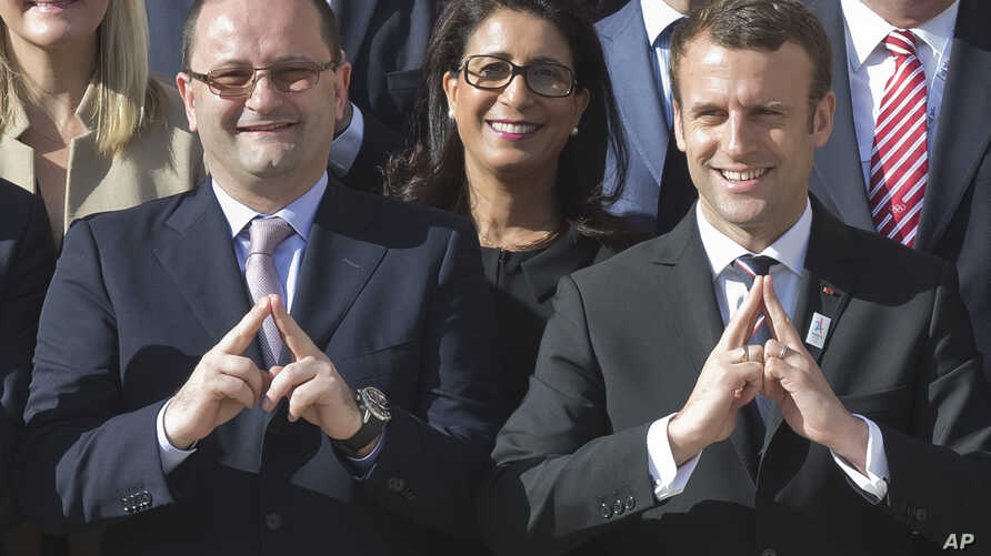 International Olympic Committee Evaluation Commission Chair Patrick Baumann, left, and new French President Emmanuel Macron make a singe representing the logo of Paris 2024 bid as they pose during a group photo at the Elysee palace in Paris, France,