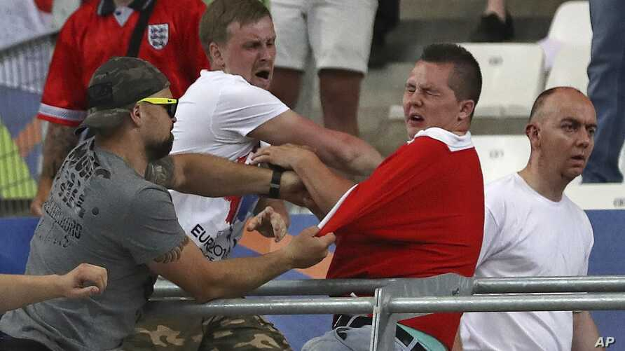FILE - Russian supporters attack an England fan at the end of the Euro 2016 Group B soccer match between England and Russia, at the Velodrome stadium in Marseille, France, June 11, 2016.