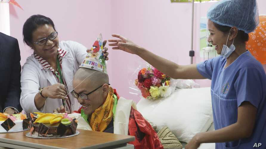 Medical staff congratulate Taiwanese trekker Liang Sheng-yueh during a birthday celebration at Grandee International Hospital in Kathmandu, Nepal, Friday, April 28, 2017. The Taiwanese man who was rescued on Wednesday after 47 days on a mountain in N