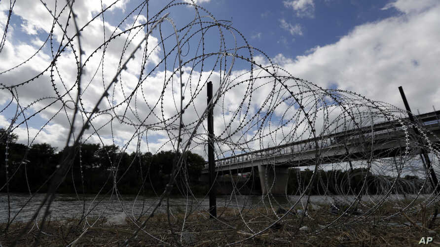 FILE - Razor wire recently placed by the U.S.military along the banks of the Rio Grande frames the McAllen-Hidalgo International Bridge at the U.S.-Mexico border, Nov. 3, 2018, in McAllen, Texas.