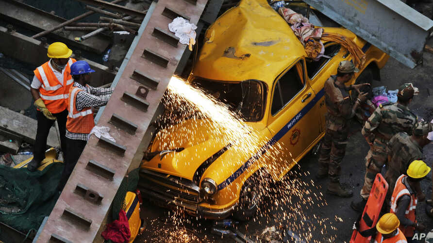 Rescue workers cut through parts of a partially collapsed overpass in Kolkata, India, March 31, 2016.