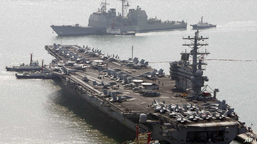 FILE - U.S. aircraft carrier USS Ronald Reagan anchors as U.S. Aegis Ship passes after they arrive at Busan port for joint military exercises in Busan, South Korea. The United States and South Korea started joint naval exercises, Nov. 11, 2017, that