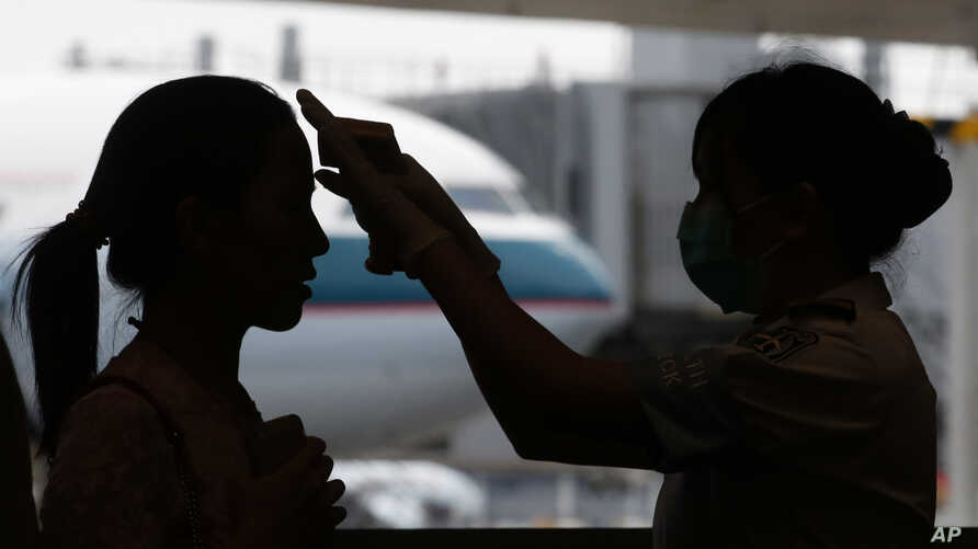 A passenger arriving from Busan, South Korea, receives a temperature check for MERS (Middle East Respiratory Syndrome) as she arrives at Hong Kong Airport, June 5, 2015.