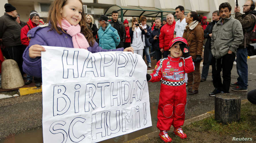 Kids celebrate with a placard the 45th birthday of seven-times former Formula One world champion Michael Schumacher in front of the CHU hospital emergency unit in Grenoble, French Alps, where Michael Schumacher is hospitalized, Jan. 3, 2014.