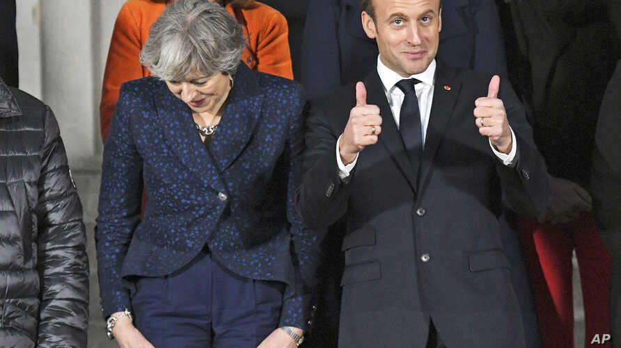 Prime Minister Theresa May (L) and French President Emmanuel Macron prepare for a group photo during UK-France summit talks at the Royal Military Academy Sandhurst, in Camberley, England, Jan. 18, 2018.