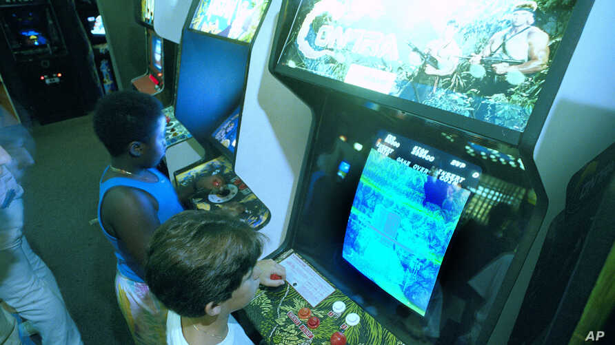 """FILE- A July 21, 1987 photo shows Carlos Tunnerman, 10, playing the """"Contra"""" video game at an arcade in a Miami, Fla."""