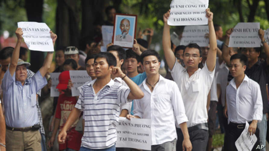 Anti-China protesters hold a portrait of late revolutionary leader Ho Chi Minh and the names of Vietnamese soldiers who were killed by China in 1974 in the Paracel Islands and in 1988 in the Spratly Islands during a demonstration in Hanoi, July 24, 2
