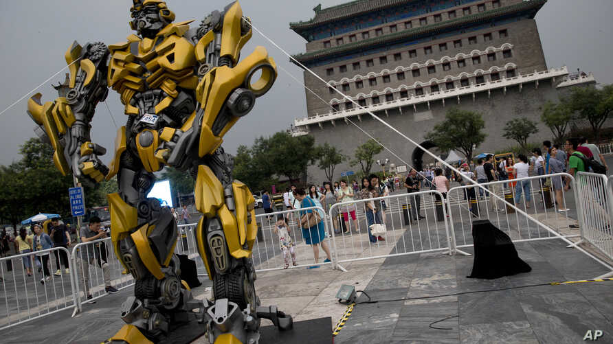 """A child stands on a barricade fence looks at a replica model of Transformers character Bumblebee on display in front of Qianmen Gate, as part of a promotion of the movie """"Transformers: Age of Extinction"""" in Beijing, China, June 21, 2014."""